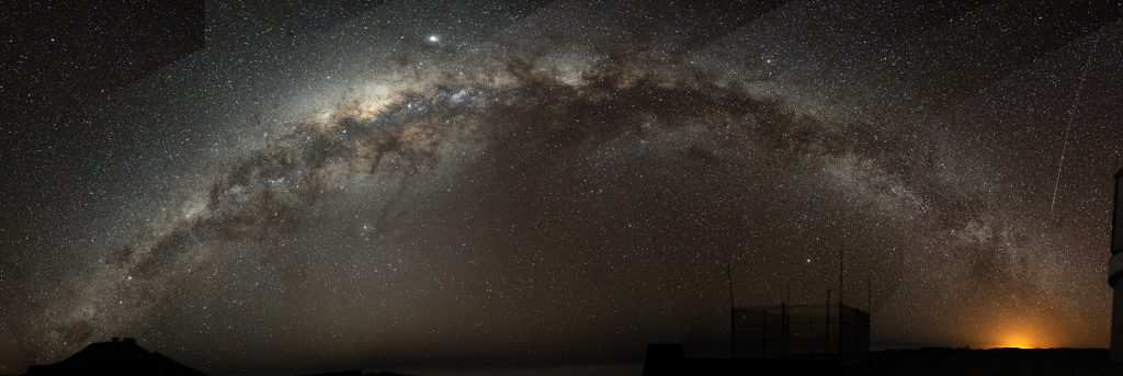 A fish-eye mosaic of the Milky Way arching at a high inclination across the night sky