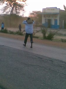 Crazy guy carrying a rock in Tala, Kenya