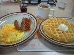 Waffle, sausage, bacon, eggs, and coffee